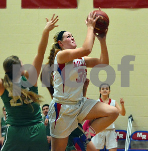 Photo by Albert J. Marro   Mill River's Tessa Davenport (32) drives the the lane during Friday's game against Springfield in Clarendon. Defending for the Cosmios was Aunna Parker (25).