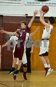Photo by Albert J. Marro  Arlington's Alex Paustian (5) couldn't reach huis man as Proctor's Nick Ojala (24) hits a jump from the side of the key during Saturday's game in Proctor. The Phantoms won.