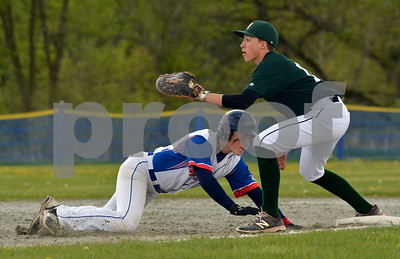 Photo by Albert J. Marro   Mill River's Jake Bishop dives safely back into first base during Monday's game against MSJ. Keaton Chapman awaits the ball for the Academy  The game was played in North Clarendon.