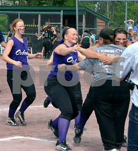Photo by Albert J. Marro Oxbow players run over to hug Coach Robin Wozny during a the celebration for the Olympians as the D-III softball champions. Oxbow defeated Leland & Gary 11-2 at Veterans Park in Poultney Saturday afternoon.