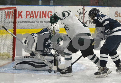 Photo by Albert J. Marro   Castleton 's Lisa Kilroy (15) attempts to puck the puck past Southern Maine goalie Whitney Padgett during Saturday's matinee game at Spartan Arena in Rutland Town. On defense for the Huskies is Delaney O'Connor (15). CU won 4-1