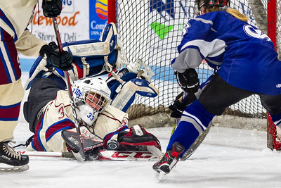 Spaulding goalie Rayna Long, left, makes a diving save in front of the net to deny U-32's Megan Ognibene, right, during Saturday's matchup in Barre.