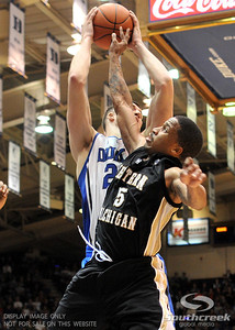 Blue Devil's Forward Miles Plumlee (Sr) is defended by Bronco's Guard Mike Douglas during the basketball game between the Western Michigan Broncos and the Duke Blue Devils at Cameron Indoor Stadium, Durham, North Carolina.  The Blue Devils defeated the Broncos 110-70.