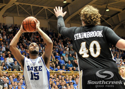 Blue Devil's Forward Josh Hairston (So) shoots against the Bronco's Forward Matt Stainbrook during the basketball game between the Western Michigan Broncos and the Duke Blue Devils at Cameron Indoor Stadium, Durham, North Carolina.  The Blue Devils defeated the Broncos 110-70.