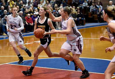 Harwood sophomore Tanum Nelson drives to the hoop past the defense of North COuntry junior McKenna Marsh for two of her game-high 21 points during the Highlanders' 47-27 seminfinal win Wednesday at the Barre Auditorium.