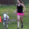 Lynn, Ma. 8-16-17. Janine Jacques and Harry finish the short race at Lynn Woods. Harry is a rescue donkey and he ran the race to highlight a race to be held on September 9 at Myopia Polo Field in Hamilton to raise money to save donkeys from being processsed in China.