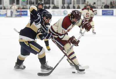 Spaulding sophomore Jamison Mast battles for the puck with Essex junior Will Couture during the first period of their game Wednesday.