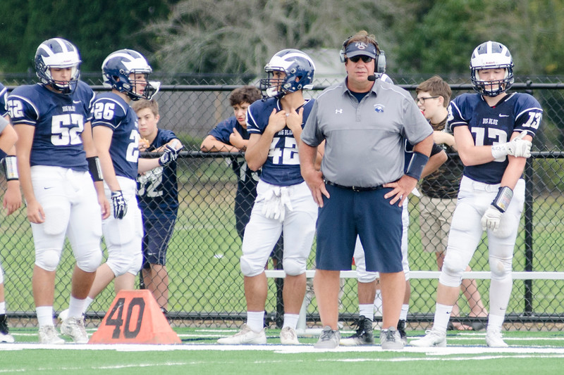 Bob Serino, second from right, watches his team from the sidelines.