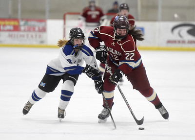 U-32 freshman Megan Ognibene and Spaulding freshman Rebecca McKelvey battle for a loose puck during the first period of their game Wednesday.