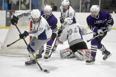 U-32 freshman Joseph Tucker clears the puck away from the goal mouth during the first period of the Raiders' game against Brattleboro Wednesday.