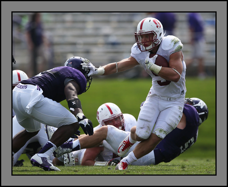 Stanford's Christian McCaffrey stiff arms a Northwestern player as he carries the ball for a first down, Evanston, Illinois, September 5, 2015. photo credit: Allen Cunningham