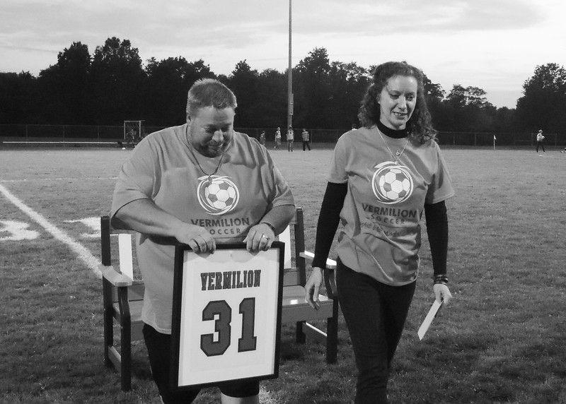 James and Christine Wojciechowski holds their son, Morgan's retired soccer jersey as they leave the bench dedicated for Morgan.