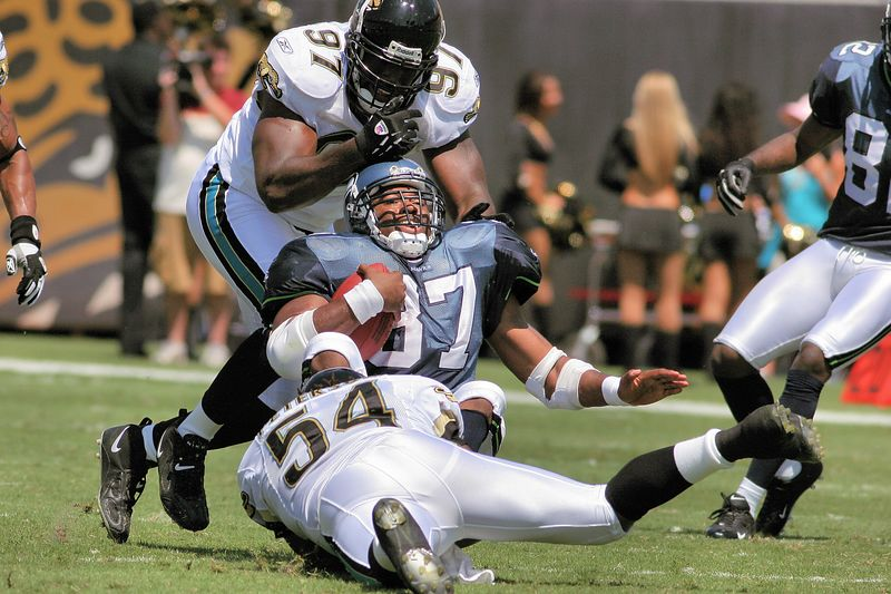 Mike Peterson (54) and Reggie Hayward (97) take down Seattle's star Running Back, Shaun Alexander (37) during the second quarter.  The Jaguars shut down the Seatlle running game, a key element in their 26-14 victory over Seattle.