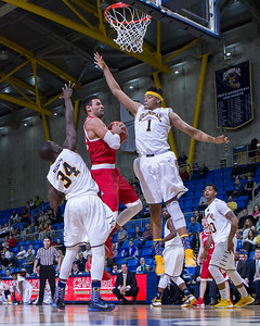 Boston University's Nathan Diedonne (22) drives the lane as Quinnipiac's Donovan Smith (1) tries to block with Abdulai Bundu (34)  Sunday at the TD Bank Sports Arena in Hamden Dec. 13, 2015 | Justin Weekes / For the Record-Journal