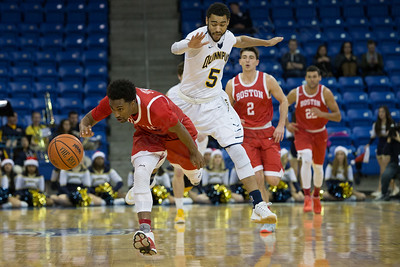 Boston University's Eric Johnson (0) chases a loose ball as Quinnipiac's Ayron Hutton (5) jumps to avoid a collision Sunday at the TD Bank Sports Arena in Hamden Dec. 13, 2015 | Justin Weekes / For the Record-Journal