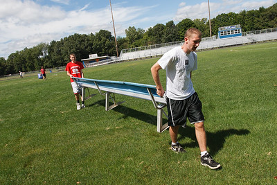 Zach Putnam 17 right and brother Ryan Putnam carry a bench to the soccer field in preparation for TWIST Friday at Lyman Hall High School in Wallingford August,15 2014 | Justin Weekes / For the Record-Journal