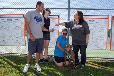 """Matt and Joanna Wayton left present a two thousand dollar check to tournament benefactor Danielle Boccher (kneeling) and Debbie Maas of Thak Dog Rescue with """"Sophie"""" a 4 year old Pit Bull mix Sunday during the Wayton Open Tennis finals at Southington High School in Southington Jul. 16, 2017 