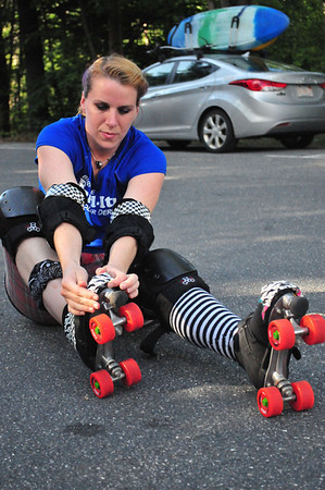 "Cheryl ""Six"" Bassett puts her roller skates on before practicing with the rest of the Berkshire Band-Itz crew on the Ashuwillticook Trail in Lanesborough, Wednesday evening July 3, 2013. Photos by Sarah Howard / Special to The Eagle."