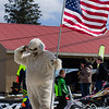 A wampa or yeti holds the flag for during  the national anthem at the Snowcross event at Bosquet Ski Resort, Saturday.