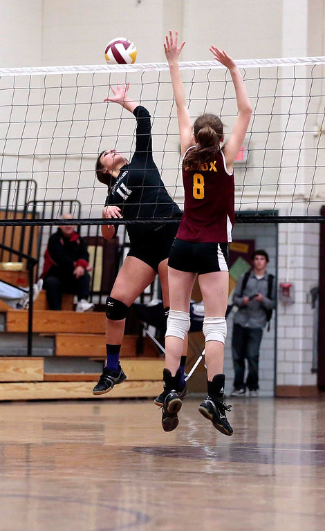 . Pittsfield\'s Sienna Carpenter jumps up to spike the ball as Lenox\'s Lizzy Barry tries to block it during a volleyball game at Lenox Memorial High School. Monday, September 23, 2013. Stephanie Zollshan/Berkshire Eagle Staff.