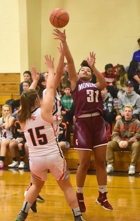 GILLIAN JONES — THE BERKSHIRE EAGLE<br /> Lee's Lydia Simone and Carly McElroy try to block Monument's Destiny Brown as she goes for the basket during the first half of a game against in Lee on Thursday.