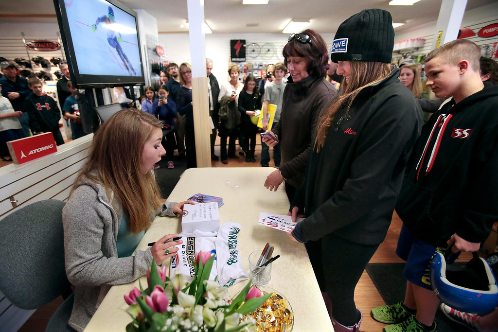 . The Bartlett family gives a box of cider donuts from their farm, Bartlett\'s Orchards, to Sochi Olympic gold medalist Mikaela Shiffrin during her visit to Plaine\'s Bike, Ski and Snowboard to meet fans and sign autographs. Wednesday, April 9, 2014. Stephanie Zollshan / Berkshire Eagle Staff / photos.berkshireeagle.com