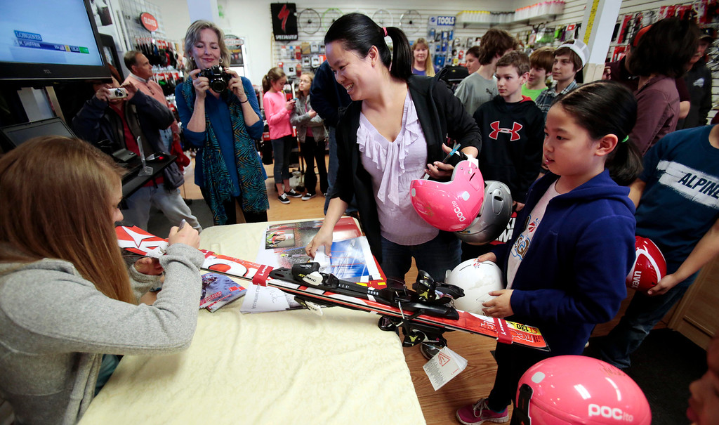 . Sochi Olympic gold medalist Mikaela Shiffrin signs a pair of skis for Abigail Eng, 9, right, during her visit to Plaine\'s Bike, Ski and Snowboard to meet fans and sign autographs. Wednesday, April 9, 2014. Stephanie Zollshan / Berkshire Eagle Staff / photos.berkshireeagle.com