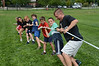 With the help of their counselor Rob Hnatonko, right, these kids do the tug of war outside the Williamstown Youth Center on Wednesday August 9, 2013 during Olympic Day, which hosted a day of athletic activities for campers. Olympic Day commemorates the birth of the modern Olympic Games and is an international effort to promote fitness, well being and the ideals of fair play, perseverence, respect and sportsmanship. (Gillian Jones/North Adams Transcript)