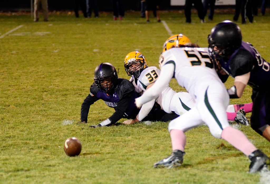 . Pittsfield quarterback Tyrell Boire and Taconic linebacker Brandon Peaslee watch as Taconic\'s Justyn Santiago prepares to jump on a fumble during the first quarter of Friday night\'s city rivalry game at Wahconah Park. Taconic recovered the fumble and scored several plays later.
