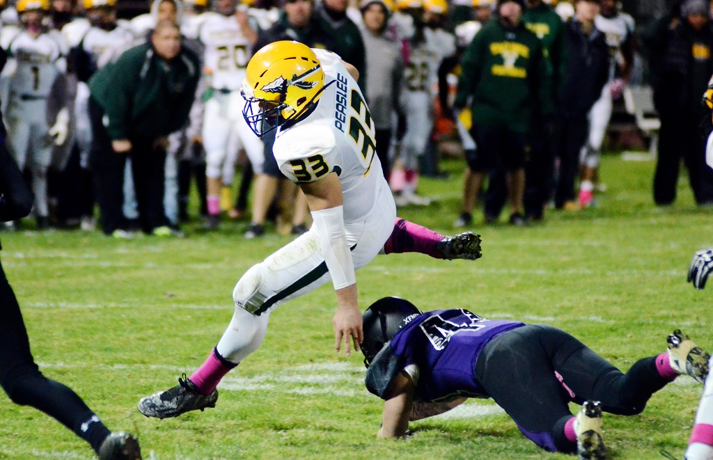 . Taconic running back Brandon Peaslee hurdles over the outstretched arm of a Pittsfield defender during Friday night\'s city rivalry game at Wahconah Park.