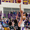 Kyle Scadlock (32) takes a shot over the outstretched hands of  Eric Sellew (33).