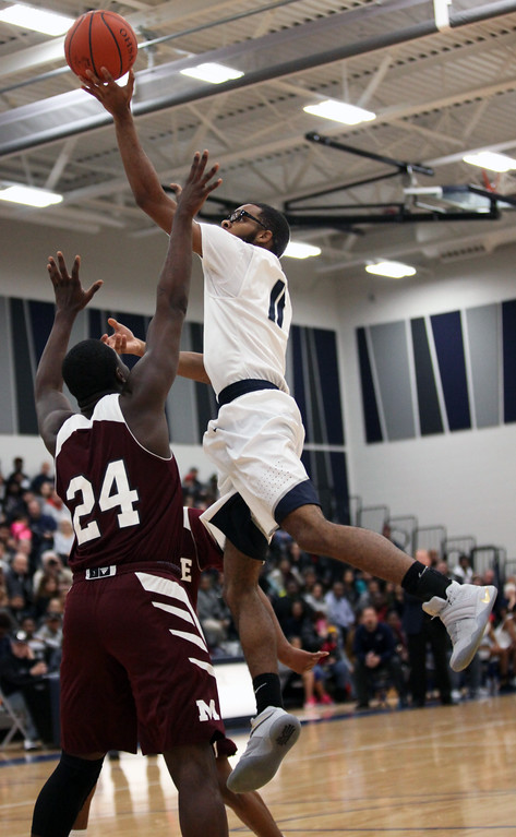 . Lorain\'s Marqua Black -Wright finger rolls a shot over Daray Mennifield of Maple Heights during the second quarter. Randy Meyers -- The Morning Journal