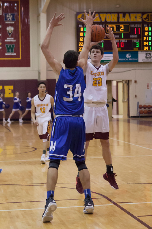 . Avon Lake\'s Creed Bologna takes a jump shot at the top of the key while Midview\'s Jonny Manning defends. Jen Forbus -- The Morning Journal