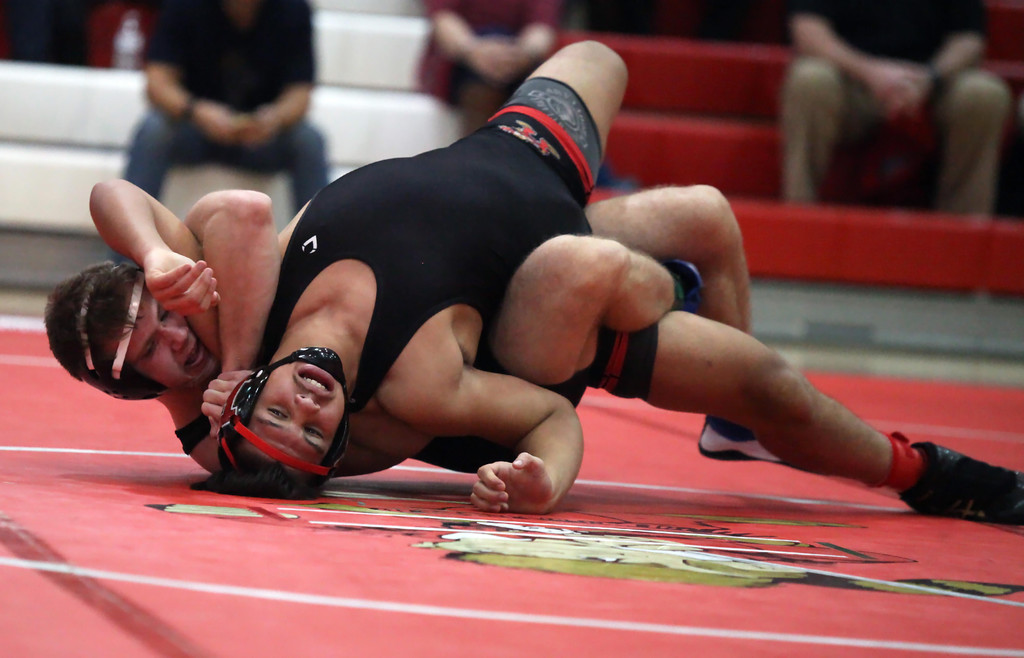 . Elyria\'s Lewis Aguilar tries to arch out of the hold by Midview\'s Trever Begin during the 182-pound match. Randy Meyers -- The Morning Journal