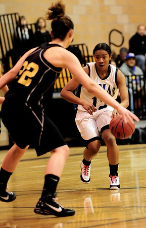 Peak to Peak's Khadijah Sayyid (right) looks for an opening while being guarded by Jefferson Academy's Nicole St. Clair (left) during their game in Lafayette, Colorado February 10, 2011.  CAMERA/Mark Leffingwell