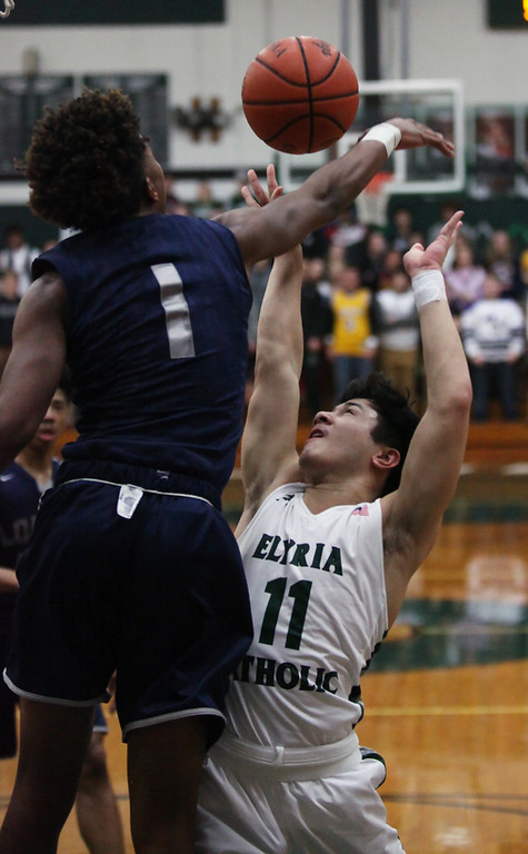 . Lorain\'s Jordan Jackson blocks the shot by Edward Wright ll of Elyria Catholic during the second quarter.  Randy Meyers -- The Morning Journal