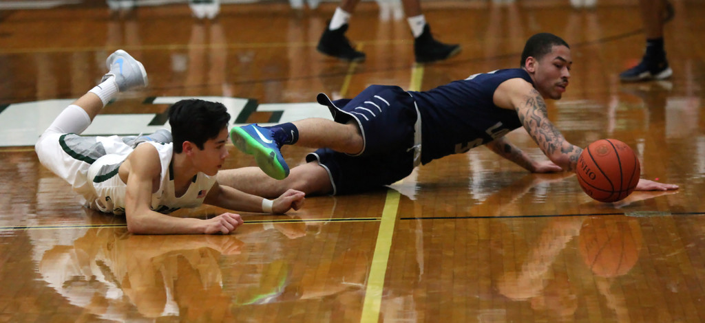 . Lorain\'s David Weatherington and Jack Griffin of Elyria Catholic dive after a loose ball during the first quarter. Randy Meyers -- The Morning Journal