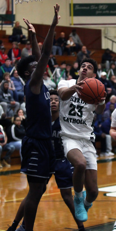 . Jarred Logan of Elyria Catholic drives against Taevon Pierre- Louis of Lorain during the first quarter. Randy Meyers -- The Morning Journal