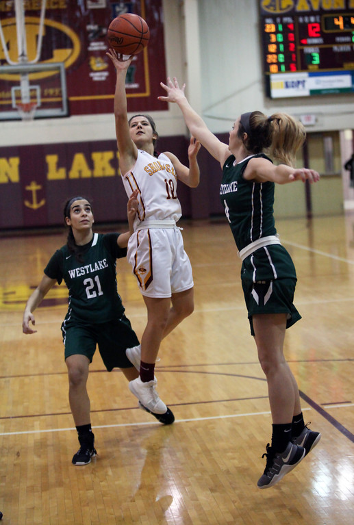 . Avon Lake guard Amber Achladis scores on a running shot in between Molli Mulder and Summer Salem of Westlake during the second quarter. Randy Meyers -- The Morning Journal