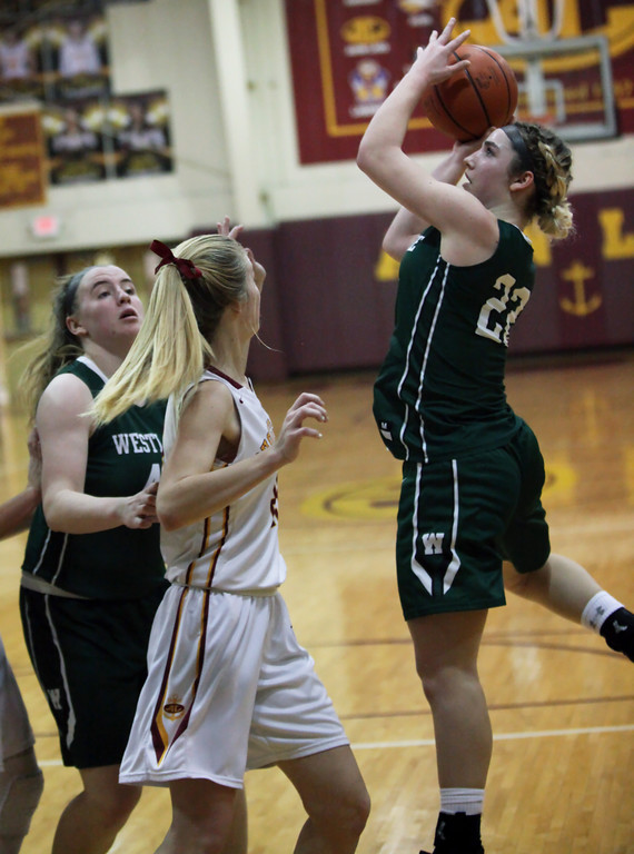 . Westlake\'s Gina Adams spins and scores over Allie Heschel of Avon Lake during the third quarter. Randy Meyers -- The Morning Journal