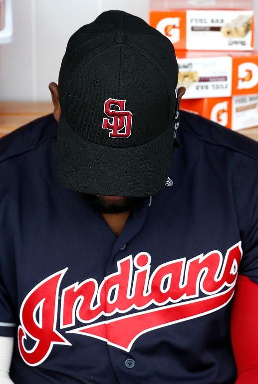 . Cleveland Indians right fielder Abraham Almonte lowers his head as he wears a cap honoring the victims of the shooting at Marjory Stoneman Douglas High School prior to a spring training baseball game against the Cincinnati Reds Friday, Feb. 23, 2018, in Goodyear, Ariz. (AP Photo/Ross D. Franklin)