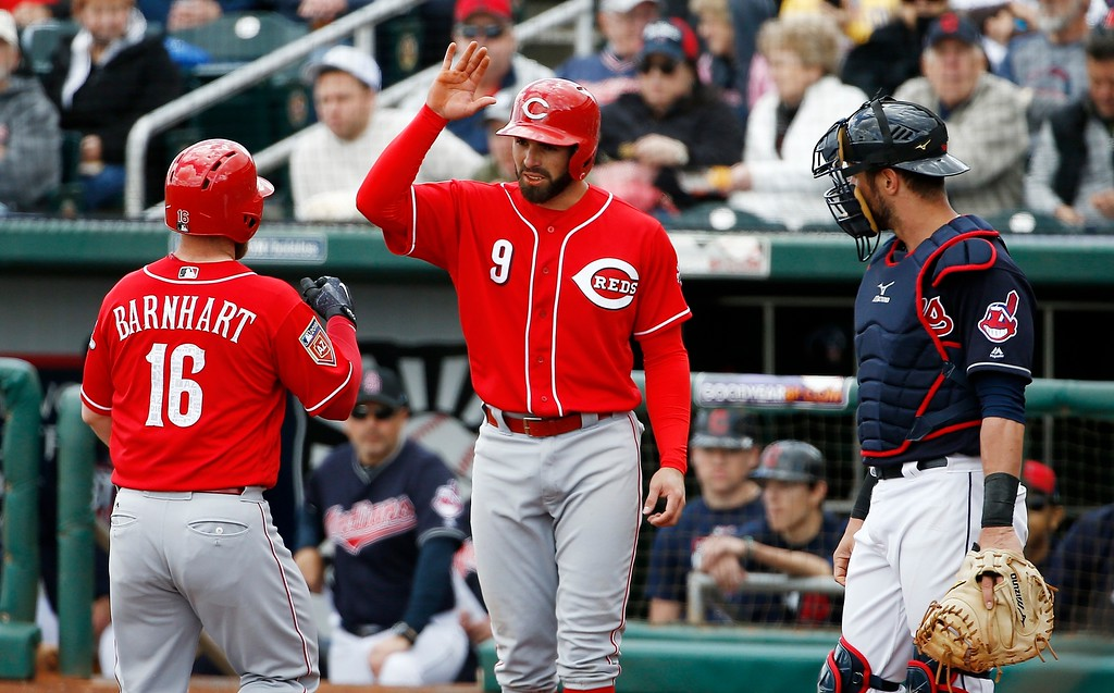 . Cincinnati Reds\' Tucker Barnhart (16) celebrates his two-run home run with teammate Jose Peraza (9) as Cleveland Indians catcher Yan Gomes, right, looks on during the third inning of a spring training baseball game Friday, Feb. 23, 2018, in Goodyear, Ariz. (AP Photo/Ross D. Franklin)