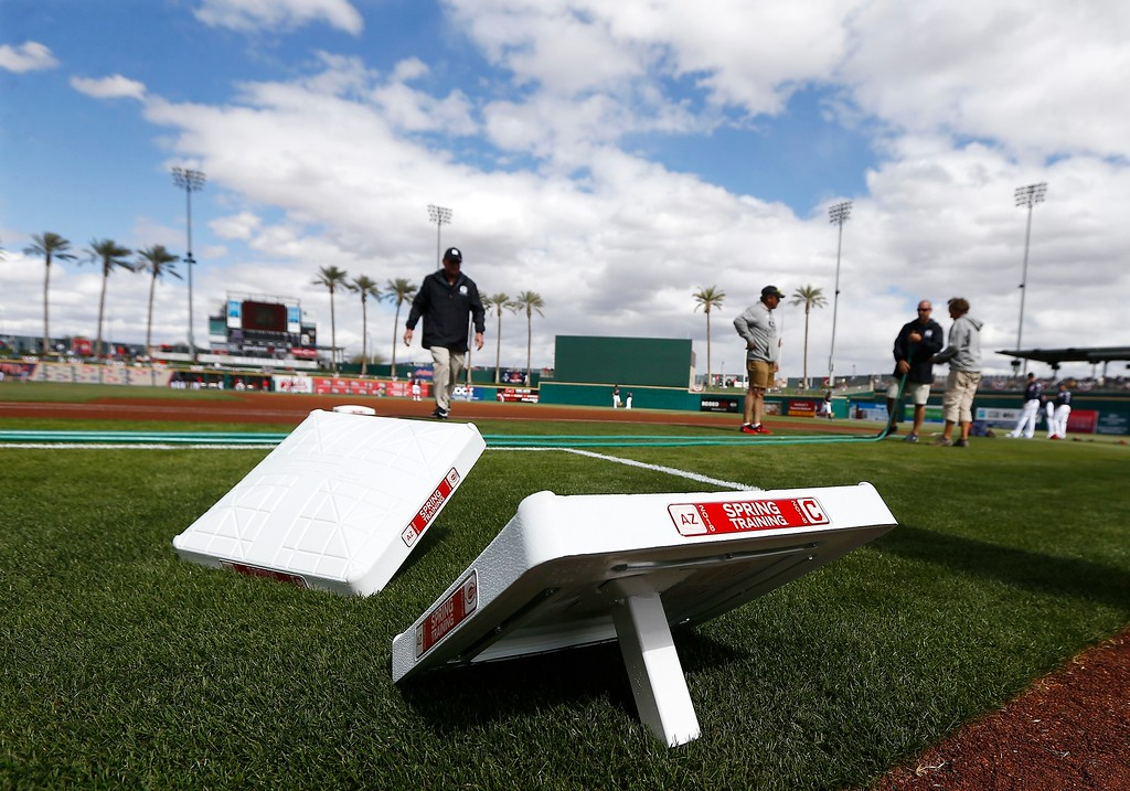 . The grounds crew prepares the field prior to a spring training baseball game between the Cleveland Indians and the Cincinnati Reds on Friday, Feb. 23, 2018, in Goodyear, Ariz. (AP Photo/Ross D. Franklin)