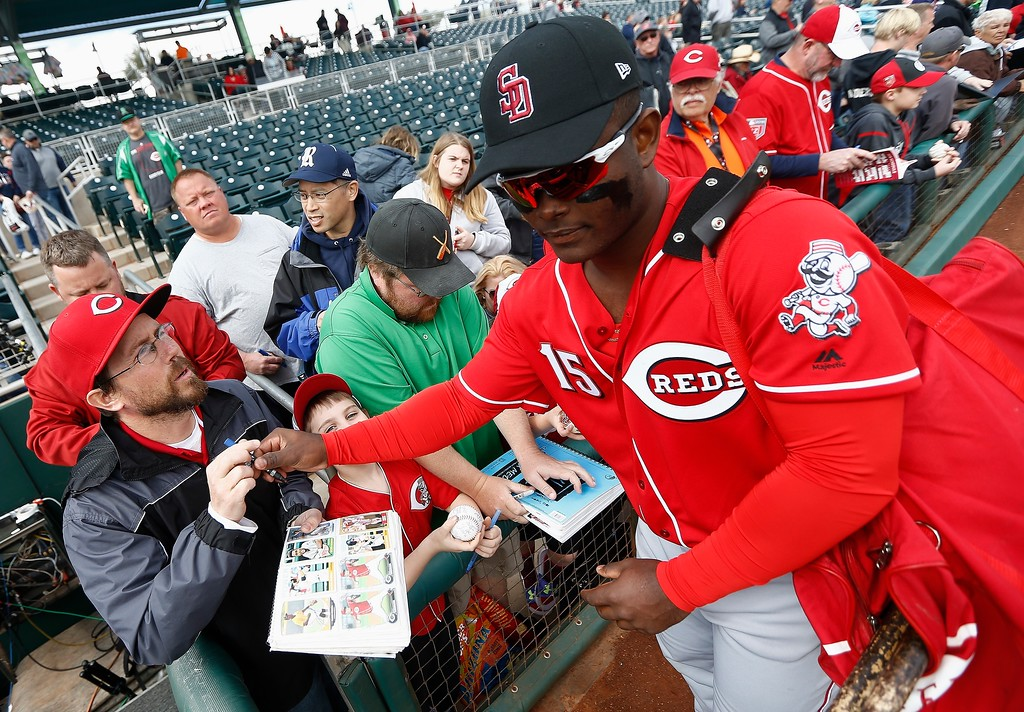 . Cincinnati Reds\' Dilson Herrera (15) signs autographs for fans prior to the team\'s spring training baseball game against the Cleveland Indians on Friday, Feb. 23, 2018, in Goodyear, Ariz. (AP Photo/Ross D. Franklin)