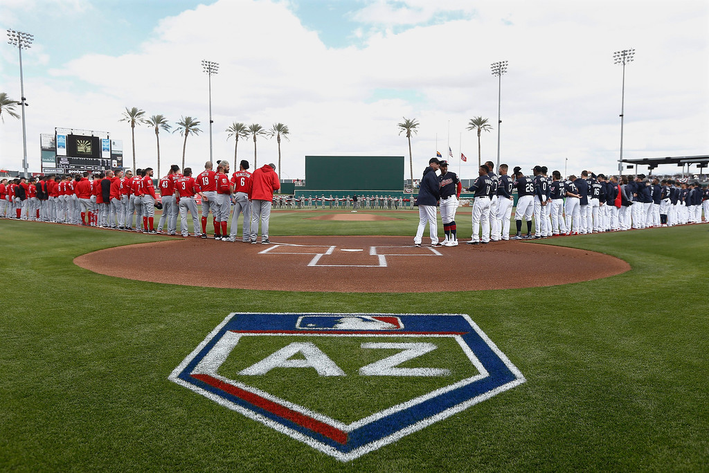 . Cincinnati Reds players and coaches, left, join Cleveland Indians players and coaches, right, for the national anthem prior to a spring training baseball game Friday, Feb. 23, 2018, in Goodyear, Ariz. (AP Photo/Ross D. Franklin)