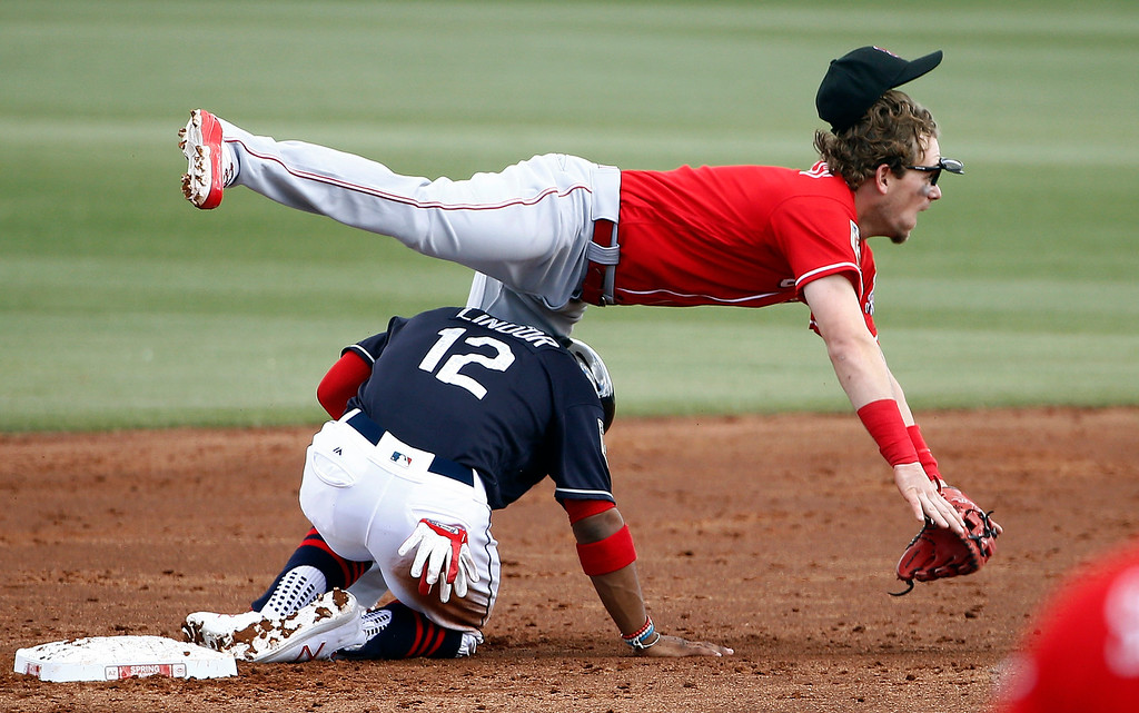 . Cincinnati Reds second baseman Scooter Gennett, right, is upended by Cleveland Indians\' Francisco Lindor (12) after Lindor was forced out at second base during the third inning of a spring training baseball game Friday, Feb. 23, 2018, in Goodyear, Ariz. (AP Photo/Ross D. Franklin)