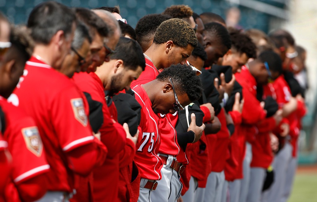 . Cincinnati Reds\' Shed Long (75) joins other players and coaches for a moment of silence honoring the victims of the shooting at Marjory Stoneman Douglas High School prior to a spring training baseball game Friday, Feb. 23, 2018, in Goodyear, Ariz. (AP Photo/Ross D. Franklin)