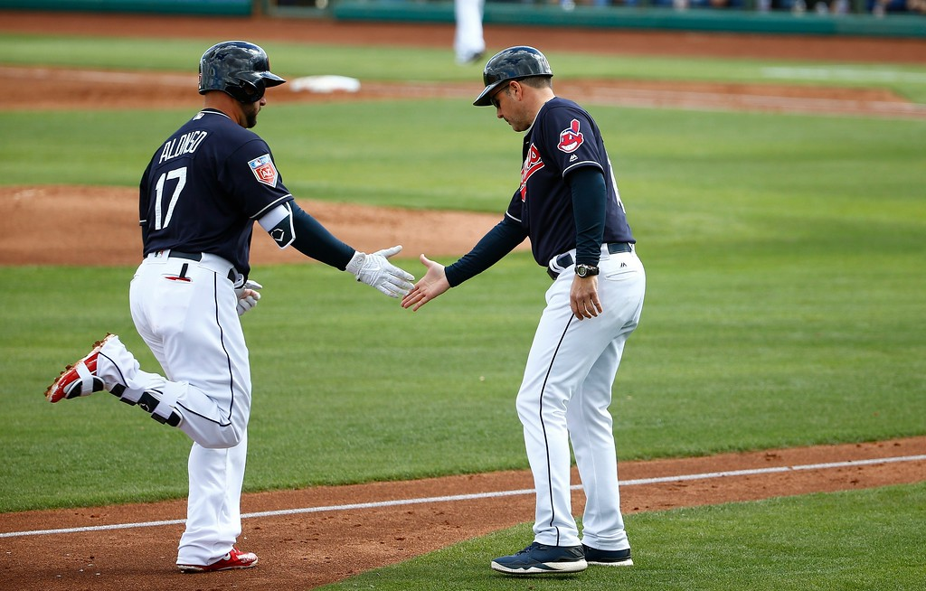 . Cleveland Indians\' Yonder Alonso (17) slaps hands with third base coach Mike Sarbaugh, right, as he rounds the bases after hitting a home run against the Cincinnati Reds during the second inning of a spring training baseball game Friday, Feb. 23, 2018, in Goodyear, Ariz. (AP Photo/Ross D. Franklin)
