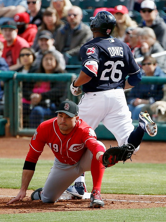 . Cincinnati Reds first baseman Joey Votto (19) reaches out to make a catch as the throw beats Cleveland Indians\' Rajai Davis (26) to first base during the second inning of a spring training baseball game Friday, Feb. 23, 2018, in Goodyear, Ariz. (AP Photo/Ross D. Franklin)