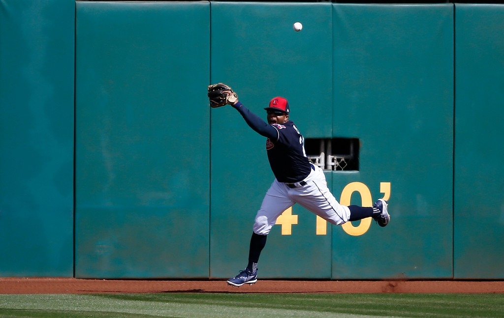 . Cleveland Indians center fielder Rajai Davis is unable to make a catch on a triple hit by Oakland Athletics\' Franklin Barreto during the third inning of a spring training baseball game Tuesday, Feb. 27, 2018, in Goodyear, Ariz. (AP Photo/Ross D. Franklin)
